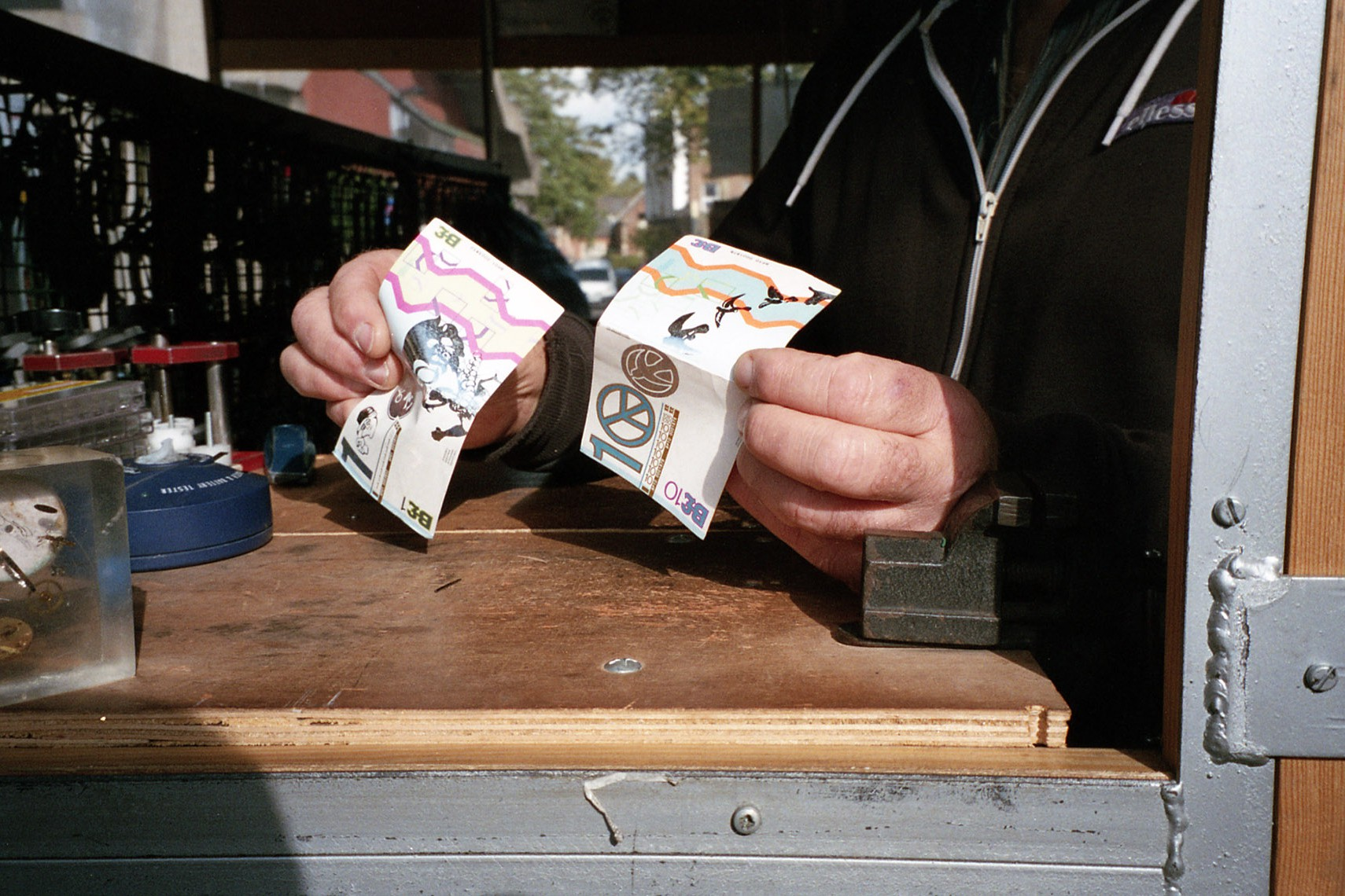 Man holds up Brixton pound.