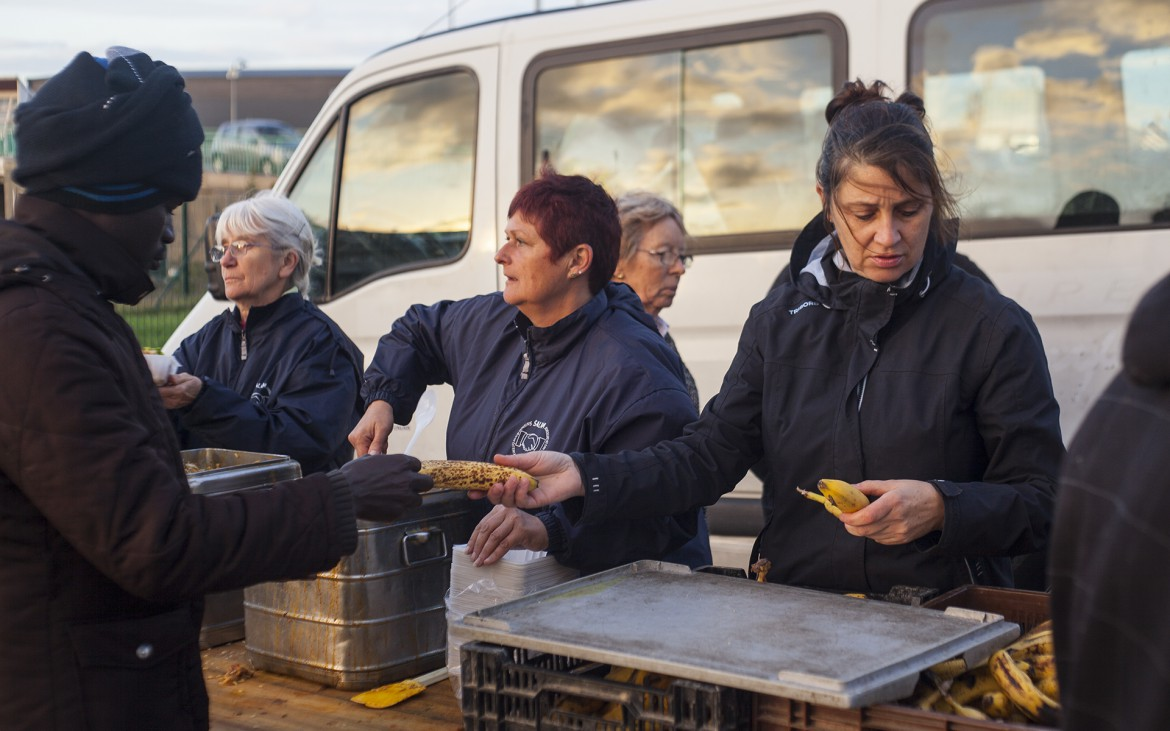Aid relief volunteers hand out food for migrants in a car park. Calais, France.