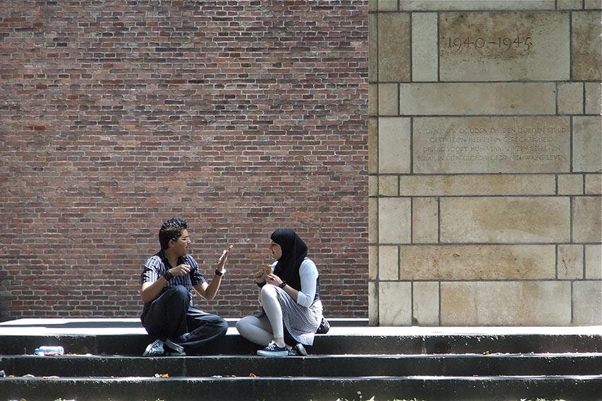 Asian couple sitting on steps talking. [Flickr: OlBrug]