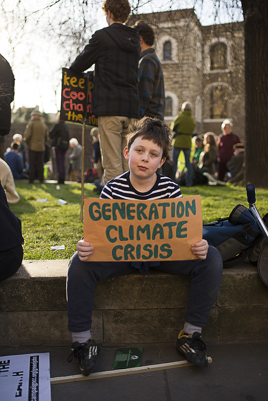 Young boy sitting on a wall holding poster. [Elena McDonough]
