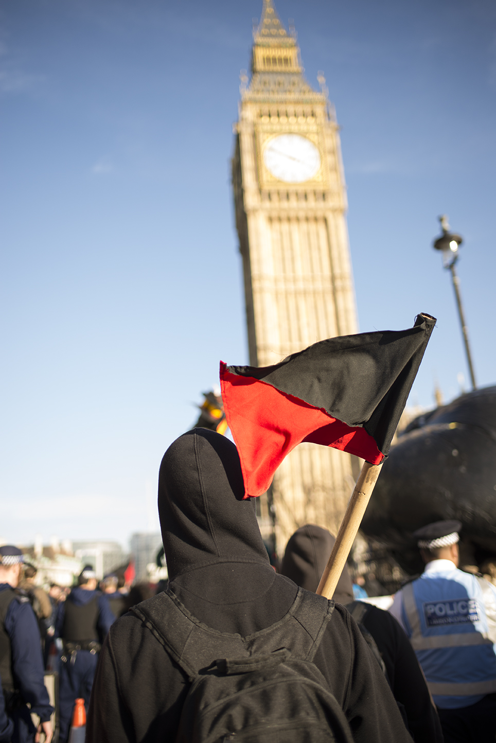 Protestor carrying black and red flag outside Houses of Parliament. [Elena McDonough]