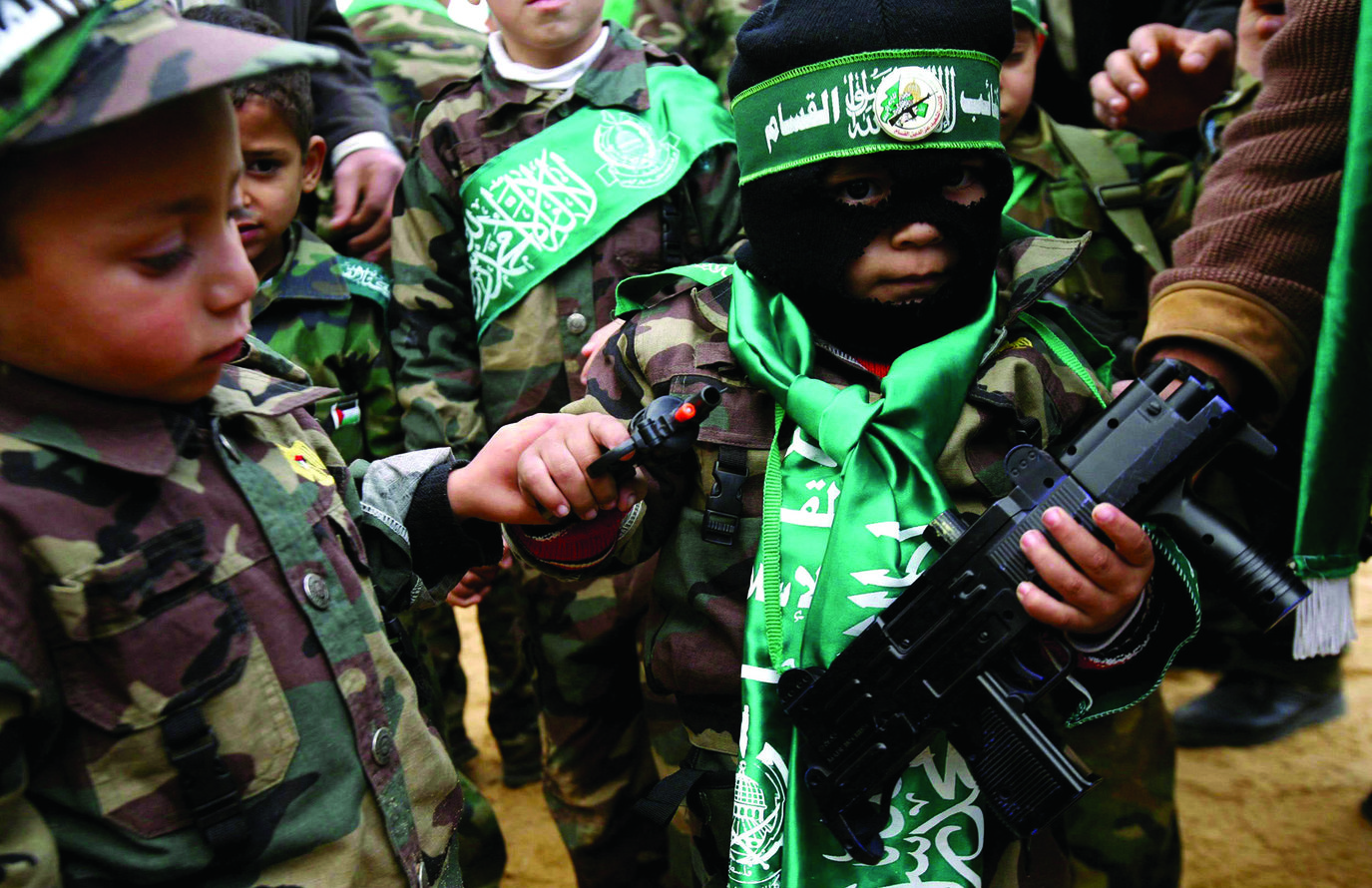 A Young  Palestinian boy dressed as a Hamas militant holds two toy guns with other small boys wearing military uniforms bearing Hamas banners during a rally  celebrating Hamas's victory in the Palestinain  parliamentary elections held at the Jabalya refugee camp.
