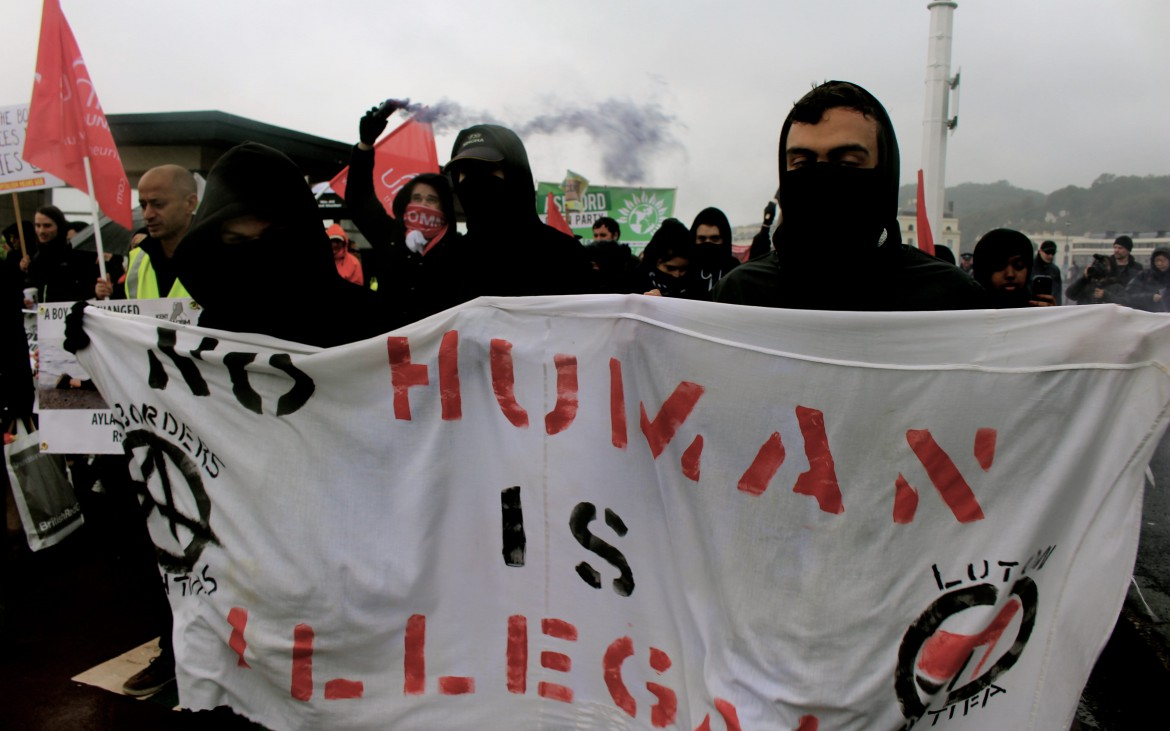 "Protestors holding a banner which says ""No human is illegal"" Photo by Hani Richter"