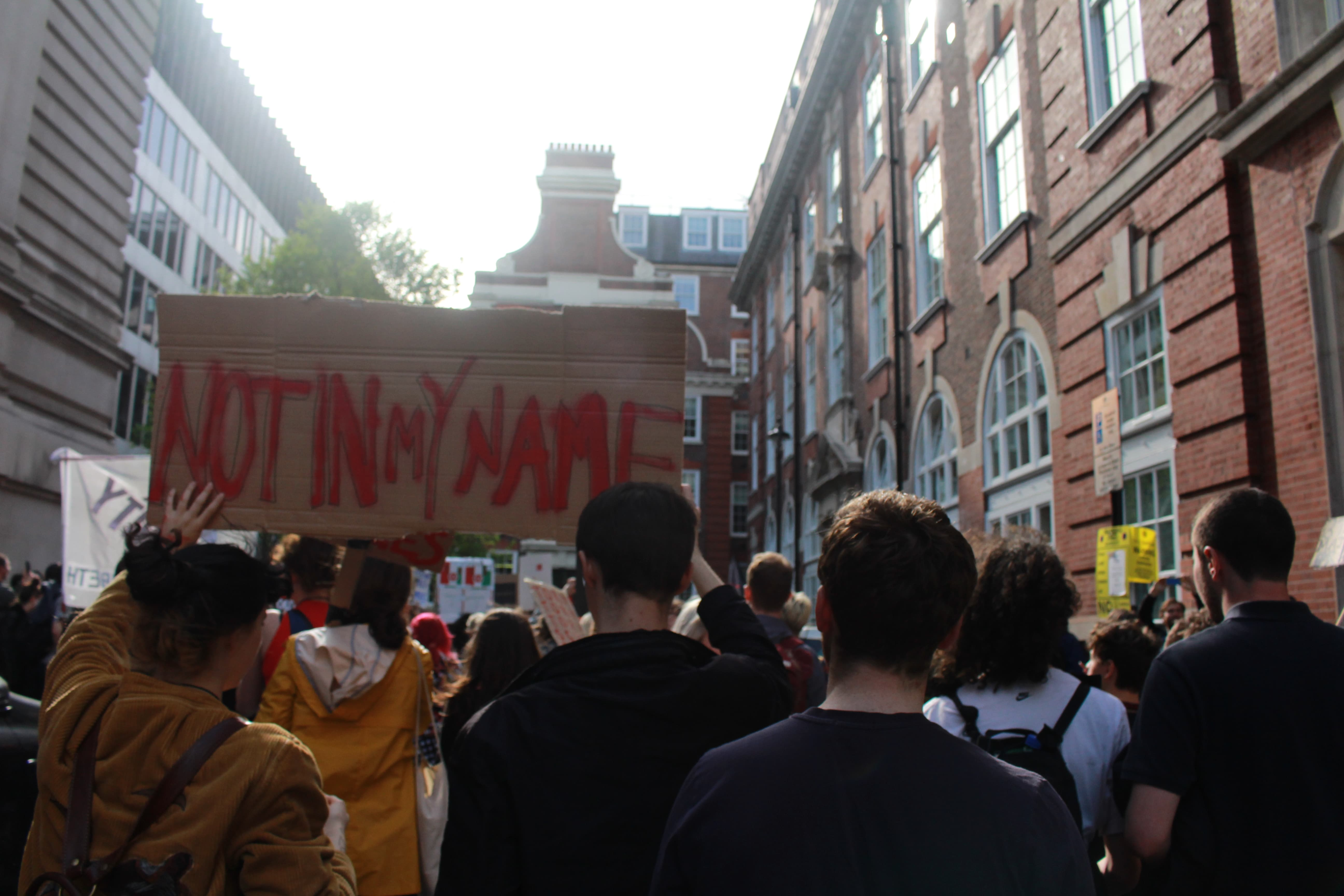 """Protestors with placard reading """"Not in my name"""""""