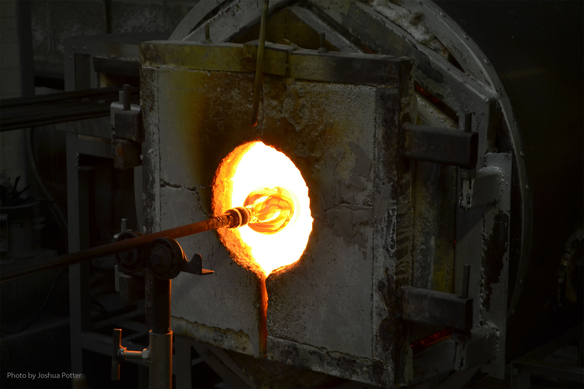A glory hole, used for reheating the piece of glass, is constantly returned to by the glassblower to shape and reshape the piece.