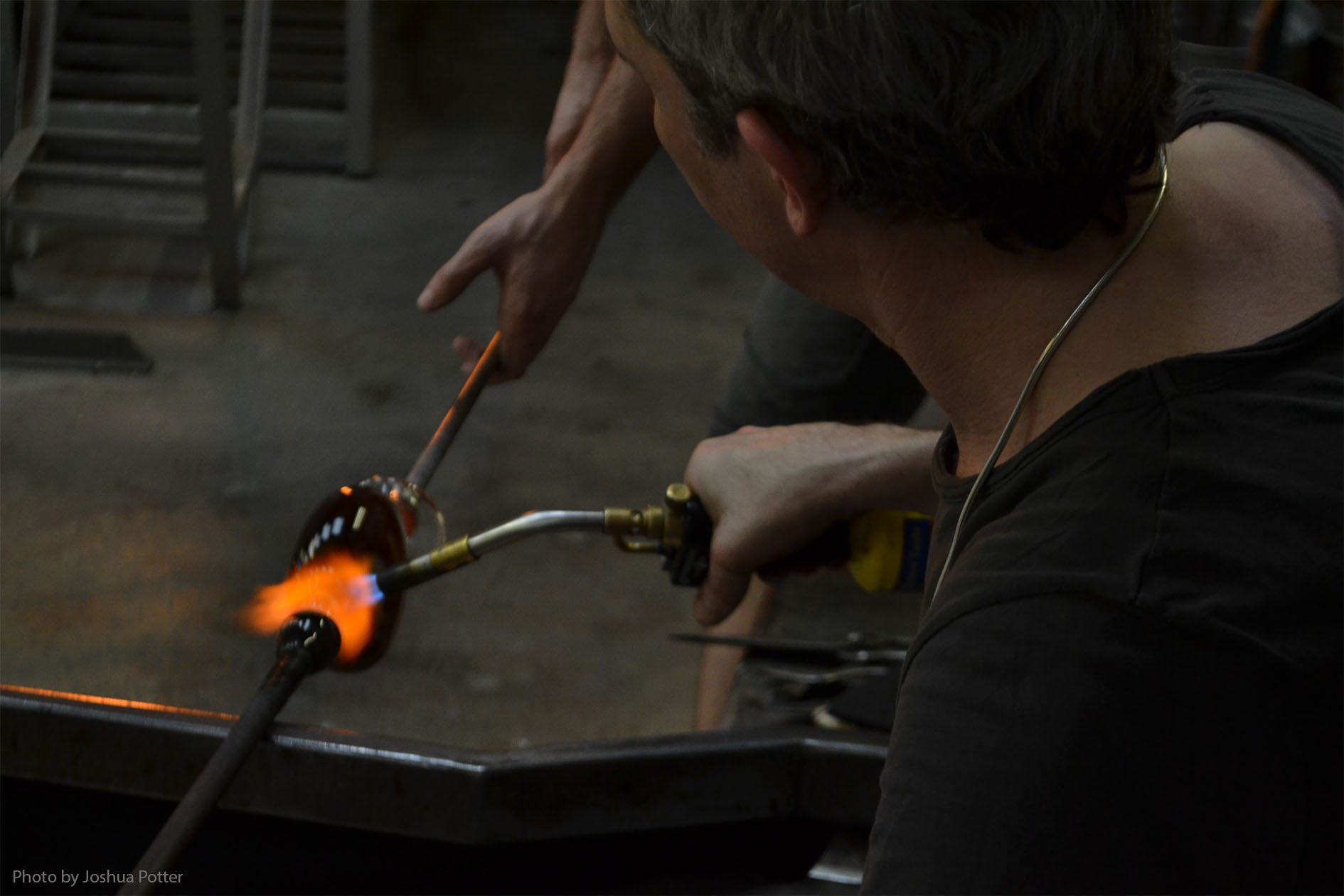 London Glassblowing was set up in 1976 by Peter Layton and was one of the first of its kind in Europe. Now turning 80, Peter himself lets the resident artists run the studio and produce most of the work. Here they have just completed the main structure of a perfume bottle and are transferring it from one worker to another, who will continue to shape and refine it.