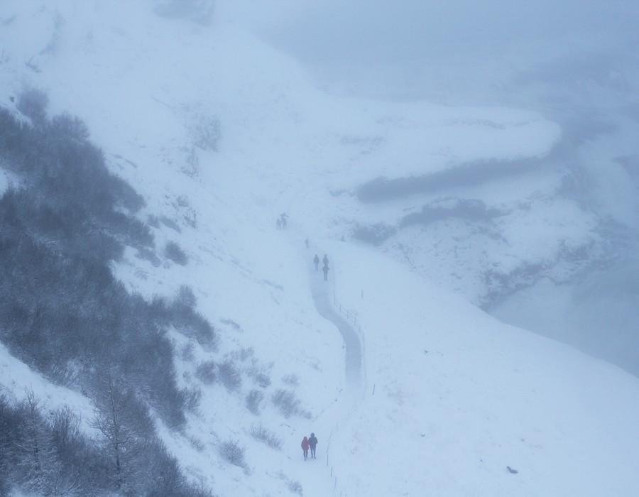 People walking along a misty snowy path