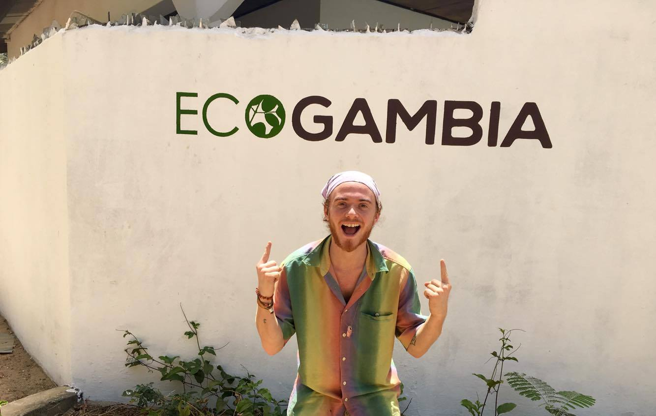 Young man posing in front of an EcoGambia sign