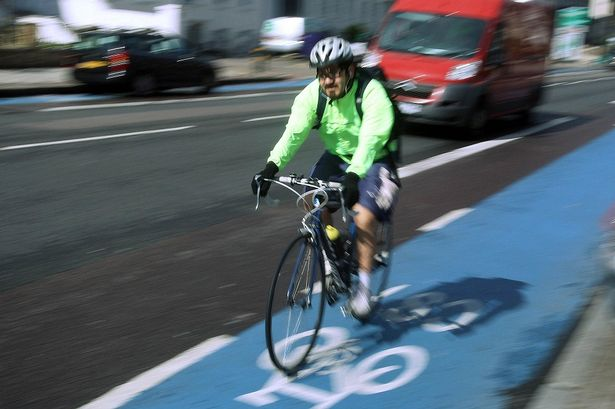 A person cycling in London using the cycling superhighway
