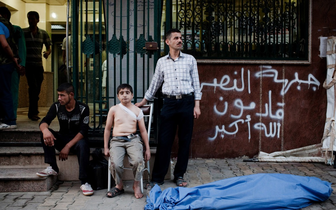 ''Ahmed, 12, from Sheikh Fares neighborhood, waits with his uncle, right, near the body of his father who was killed by a shell in the Sha'ar neighborhood of Aleppo, Syria, on Friday, August 24, 2012. Ahmed, who saw his father die, was also injured in his back by shrapnel''. - Nicole Tung
