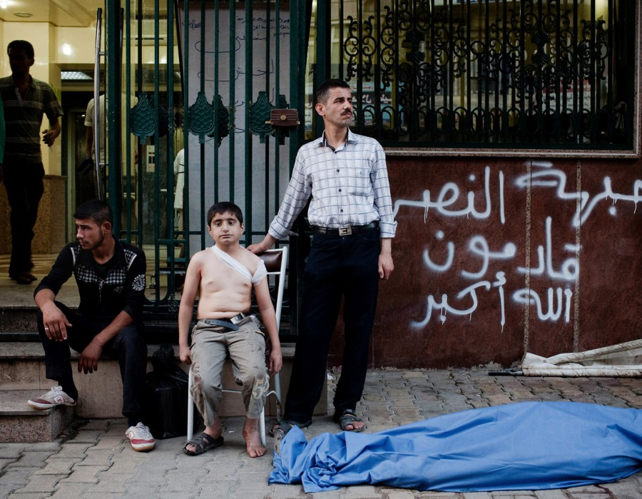 Man and boy standing by a body bag in Aleppo