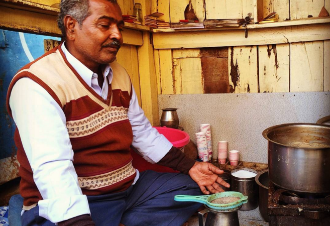 A chaiwalla meditating next to a brewing cup of chai.