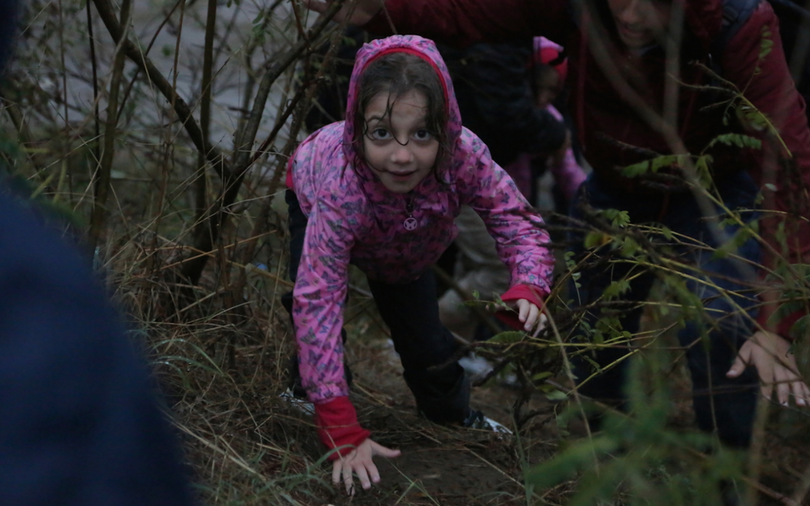 A refugee child climbing through bushes.