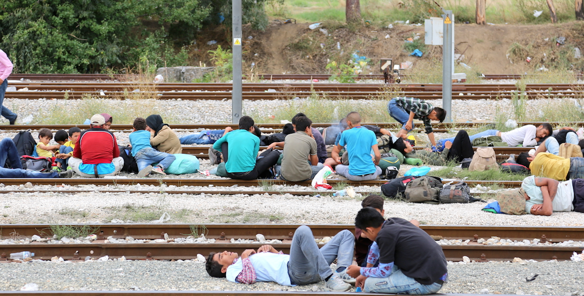 Refugees waiting for the border to open, sitting on the train tracks