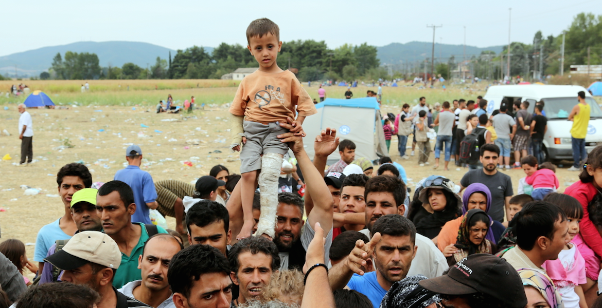 A refugee child being held up above a crowd of adults