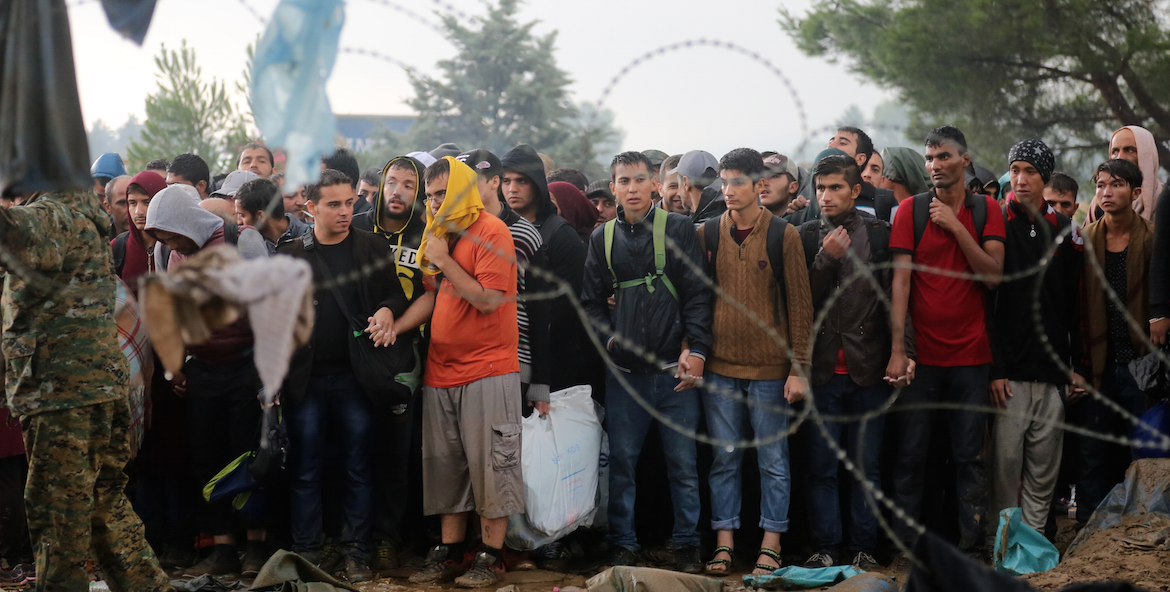 Refugees stad behind a barbed wire fence.