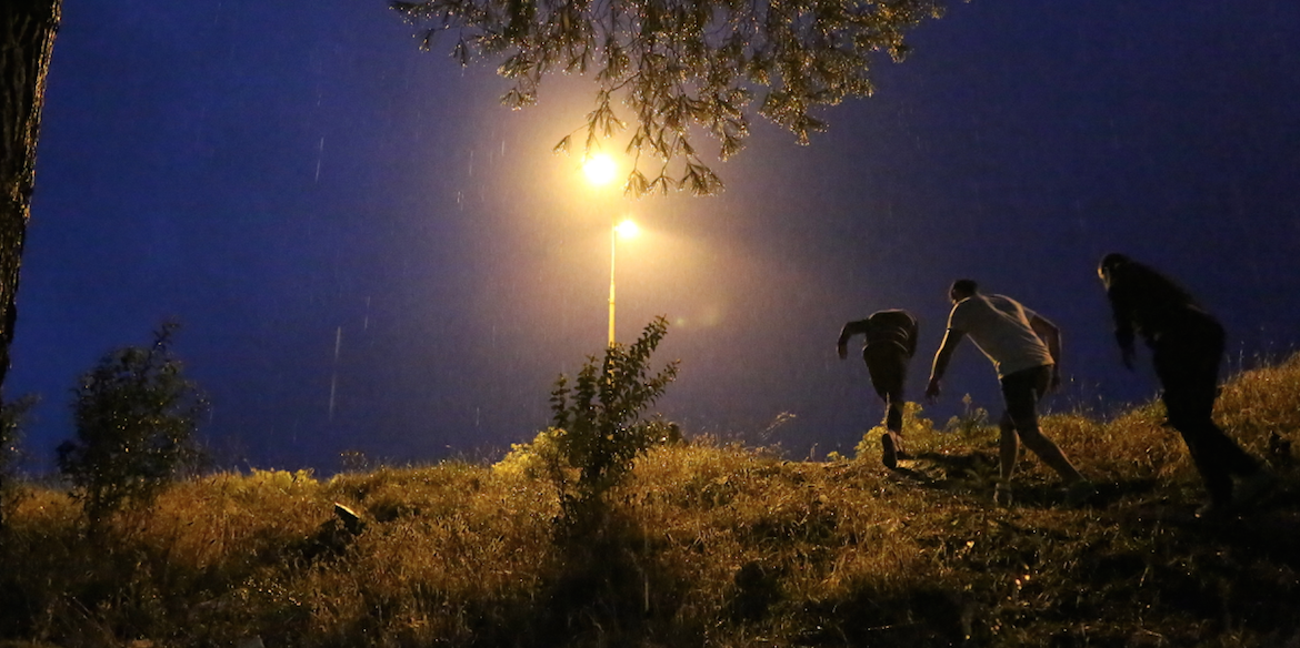 Three refugees climb up a hill at night in the pouring rain.