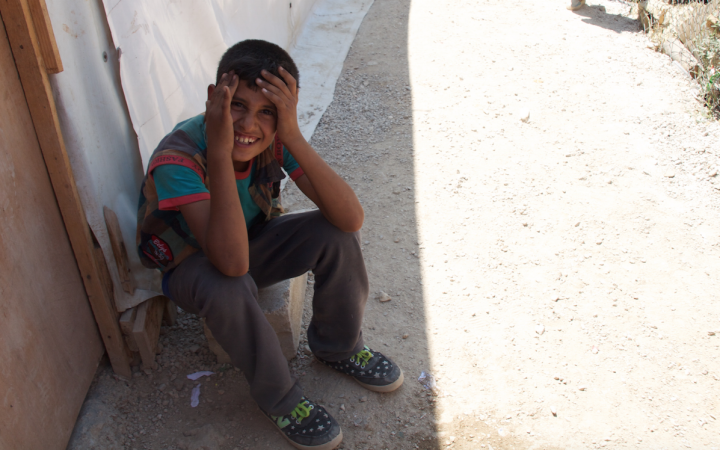 A boy sitting in the shade of a refugee tent.