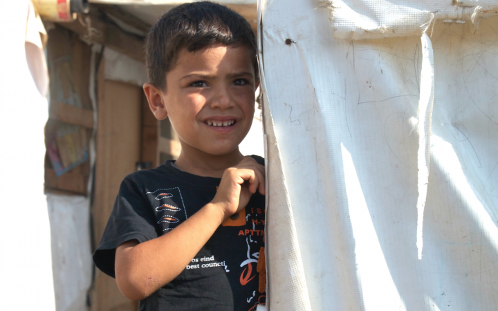 A Syrian boy peers out from behind a refugee tent.