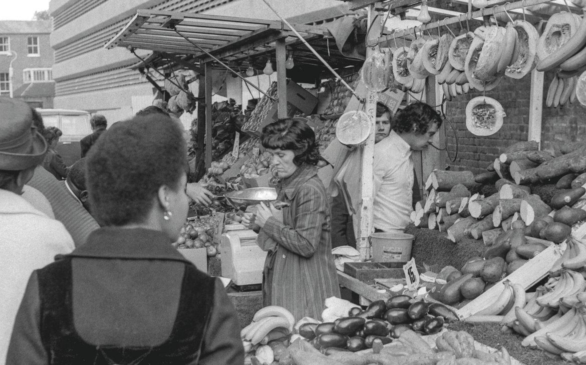 A black and white photo of a market stall in Brixton