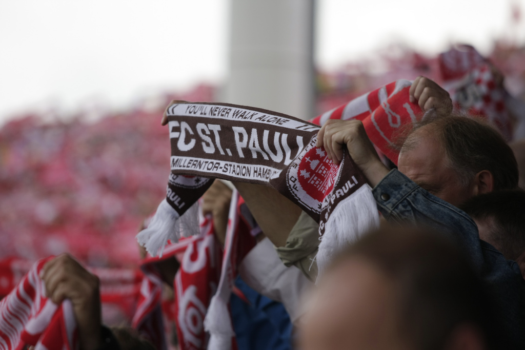 A Yorkshire St. Pauli supporter at a match, holding up his FC. St. Pauli scarf.