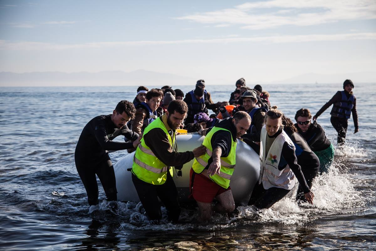 NGOs volunteers pulling a boat full of refugees off the coast