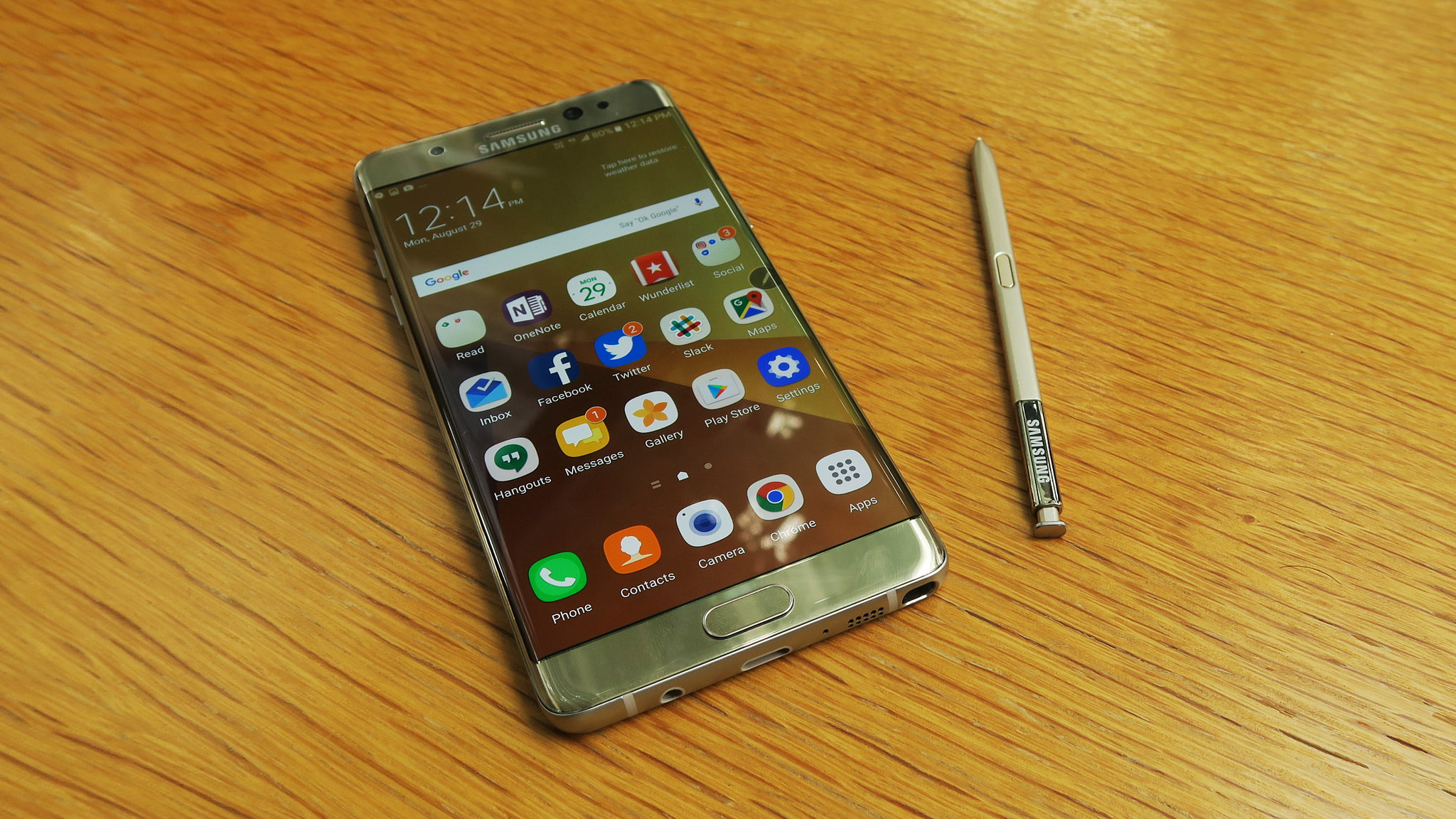 An image of a Samsung Galaxy Note 7 sits on a wooden table placed net to an pressure sensitive S (stylus) pen