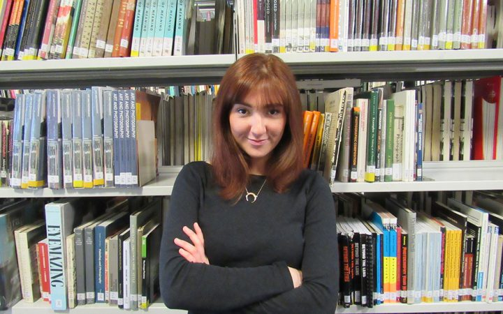 Foreign student, Ali Dominguez, standing in front of library books at LCC