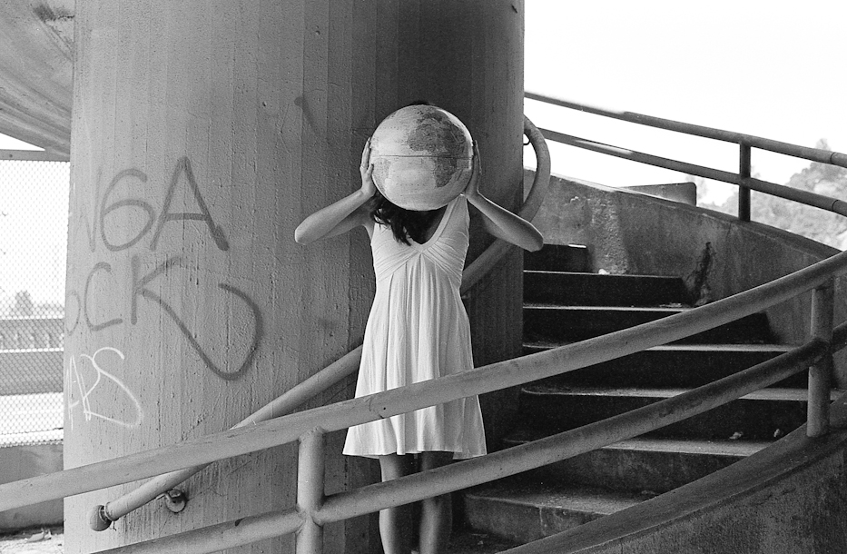 B&W image of girl holding globe in front of face