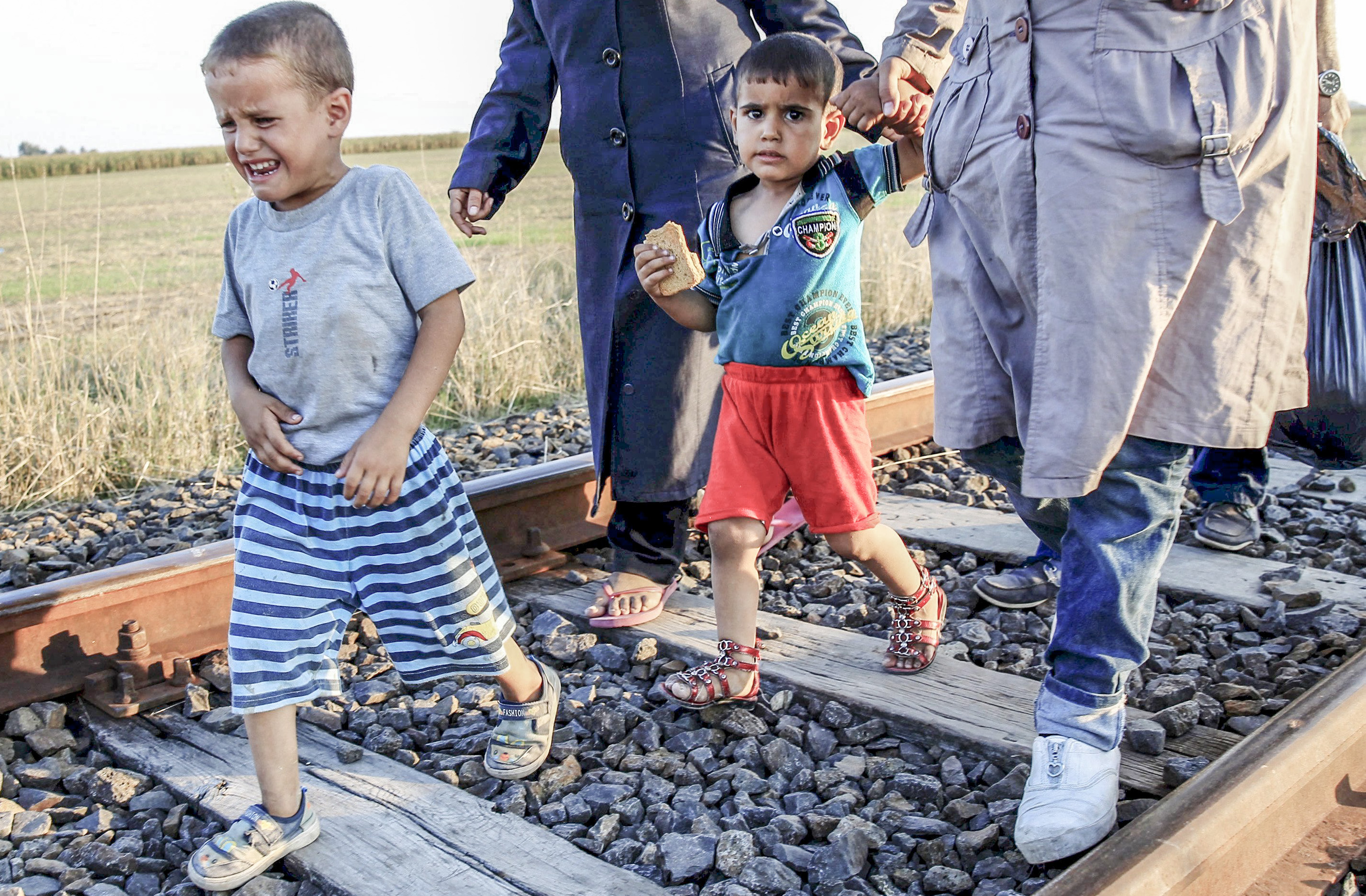 A migrant boy cries as he walks on a railway track after he crossed the Hungarian-Serbian border near Roszke, Hungary August 27, 2015.