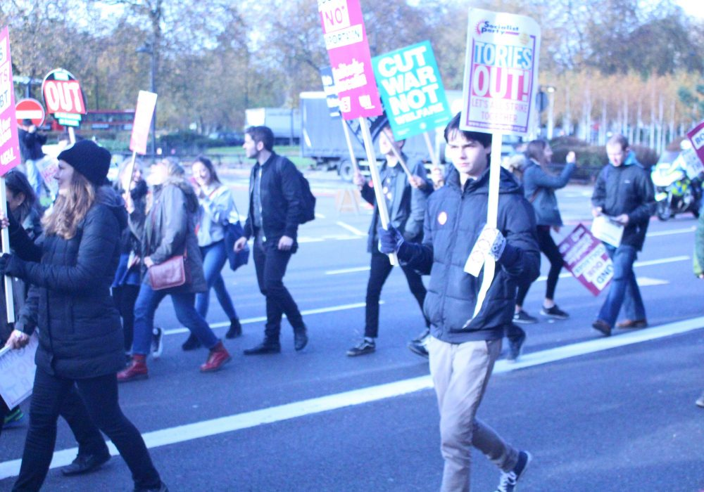 Students protesting and holding placards against government attacks to education