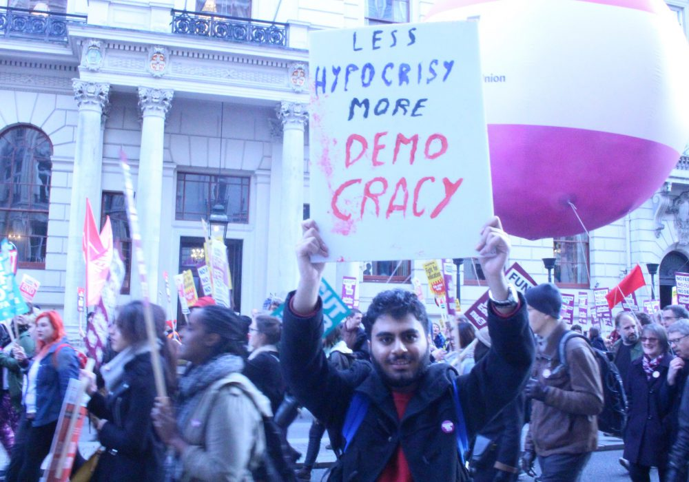 Protester poses in front of camera with placard at national demonstration
