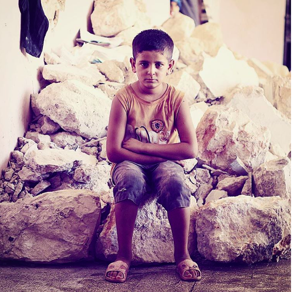A young boy sitting on a rock