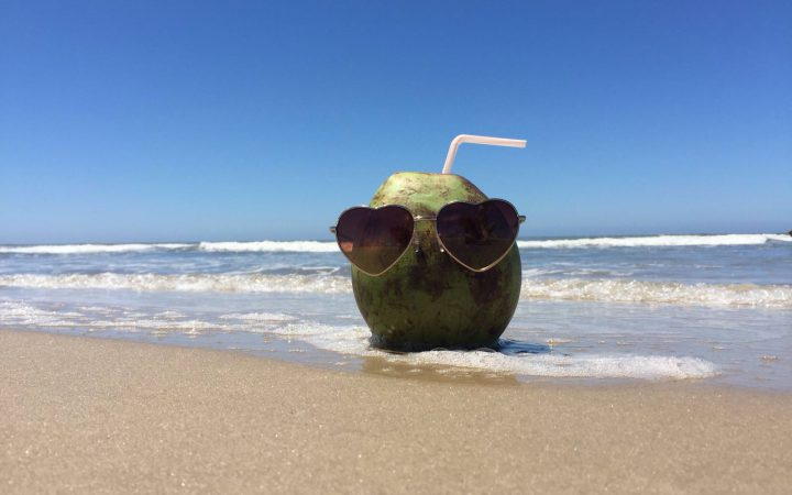 a coconut is on the beach wearing sunglasses which makes it look like a person