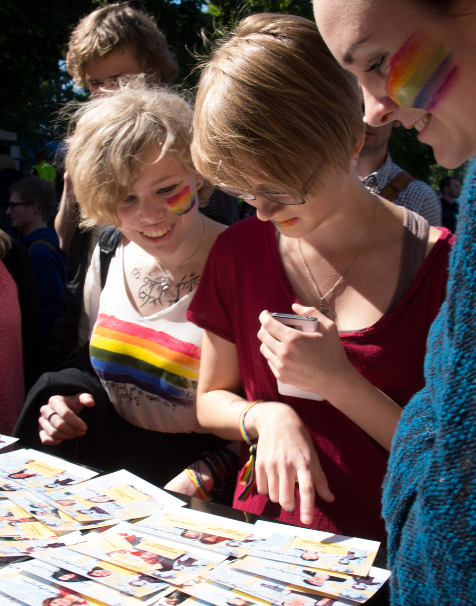 Trans Helsinki participators who have decorated themselves with rainbow flags and are looking at Amnesty's illustrated petition. Photo by Amnesty Finland, used under creative commons licence.