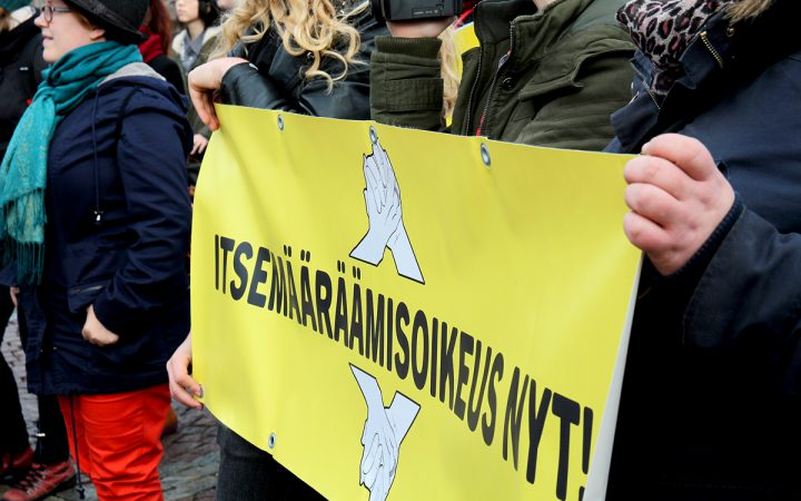 """Protesters holding a sign that says """"Self-declaration now!"""" in Finnish"""