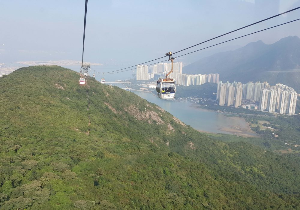 Ngong Ping 360 cable car travelling past the mountains in view of the Island below