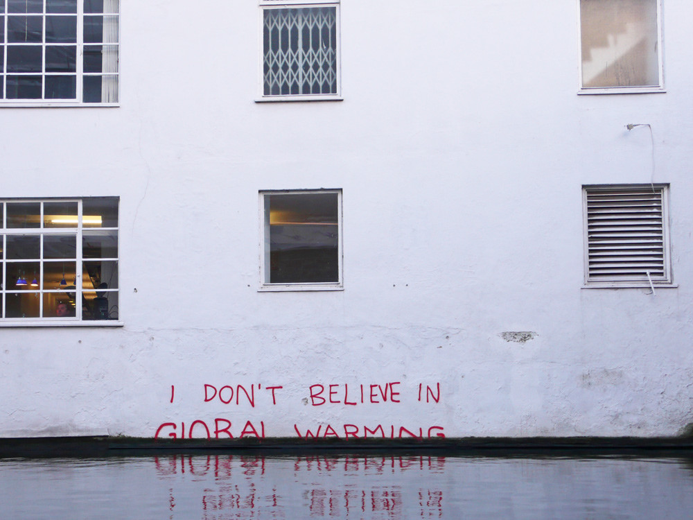 """Image of a flooded building with the word """"I don't believe in global warming"""" semi-submerged on the wall"""