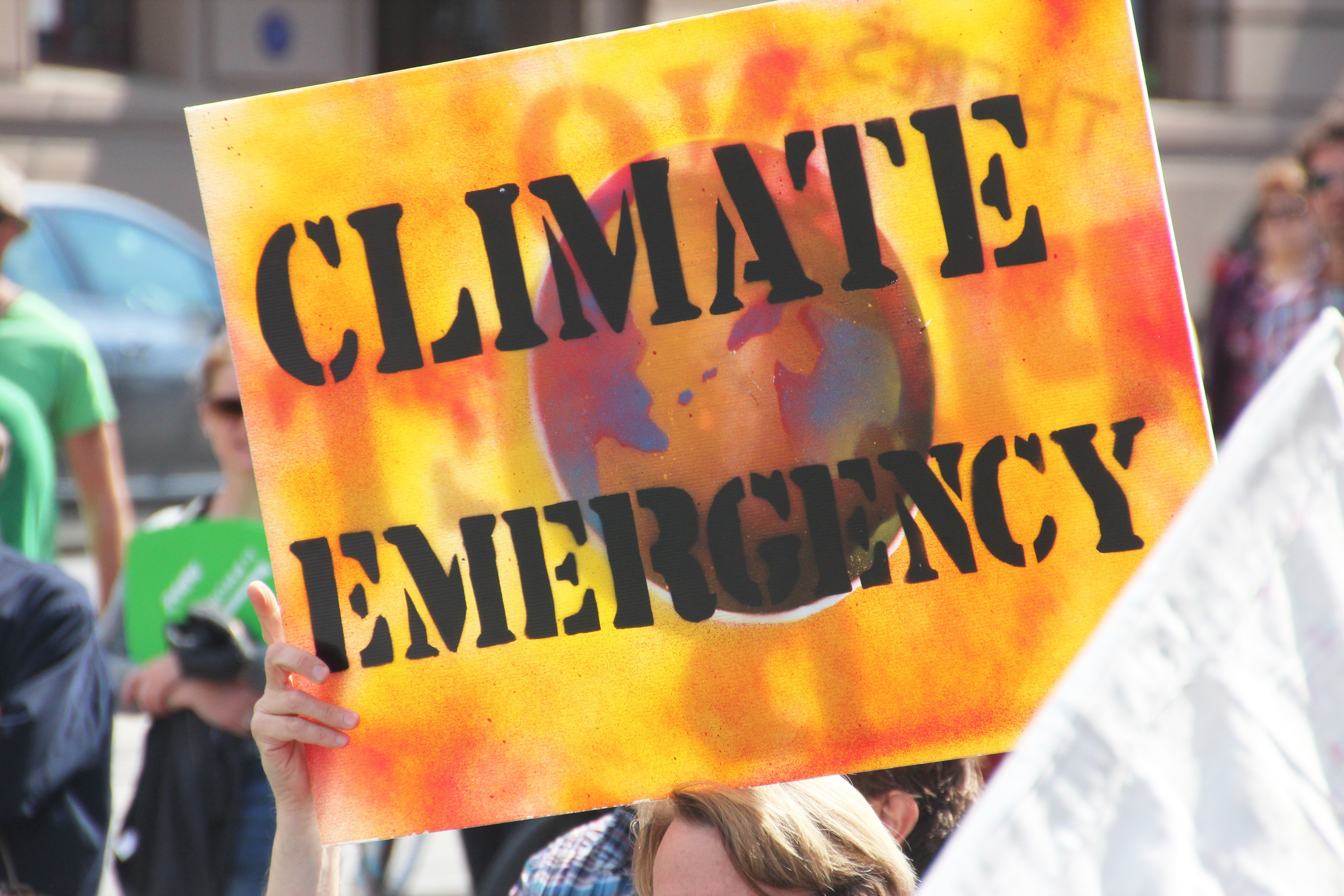 orange sign that reads 'climate emergency'