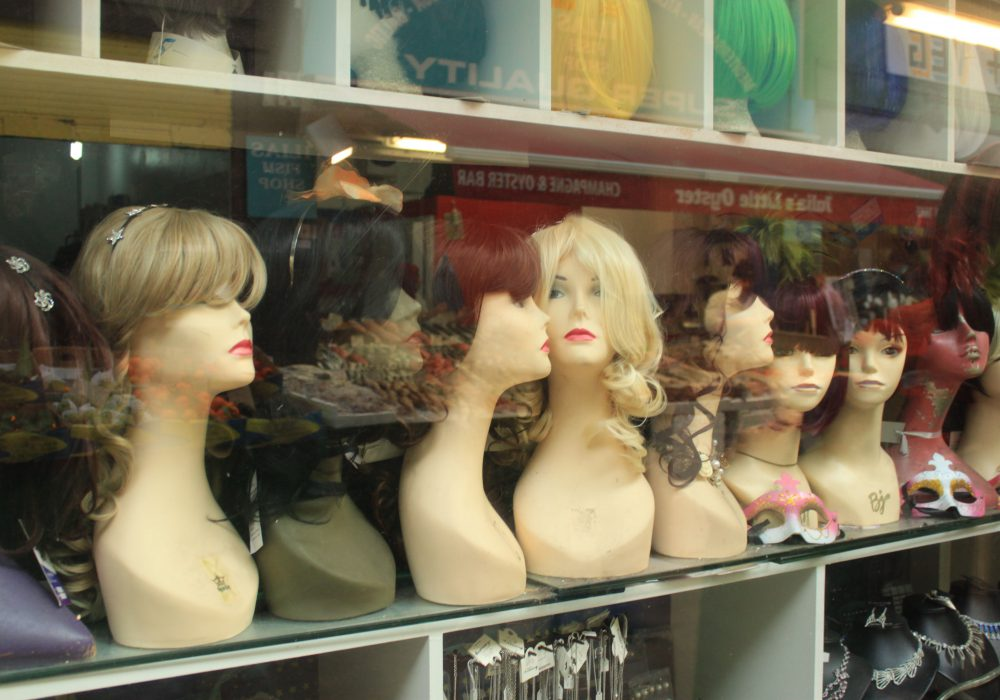 Wigs on display in a shop window