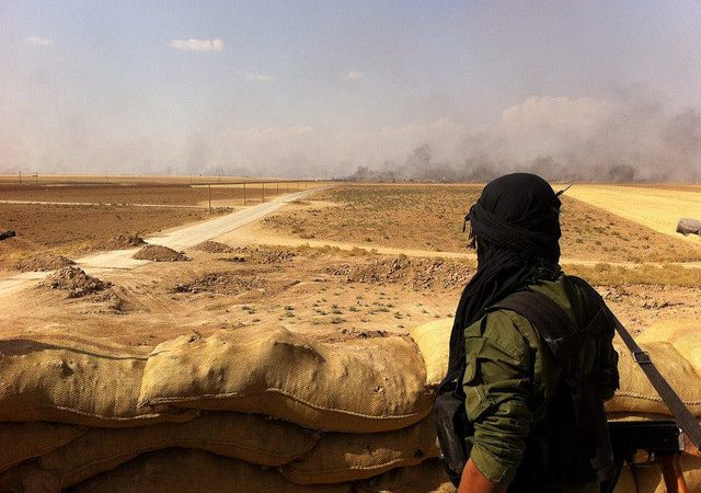 A Kurdish Fighter looks on as smoke rises in the distance