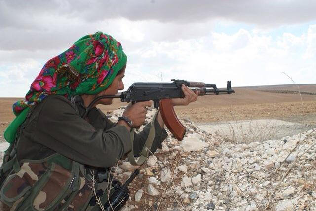 Female fighter of the YPJ points her weapon at the enemy