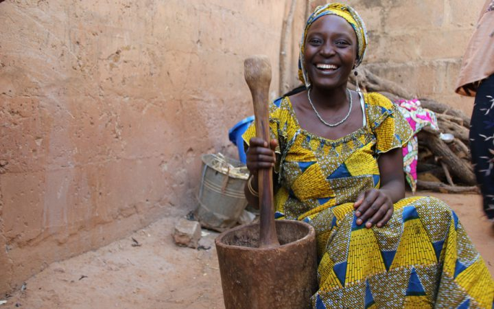 Nigerian lady making food in traditional large pestle &mortar