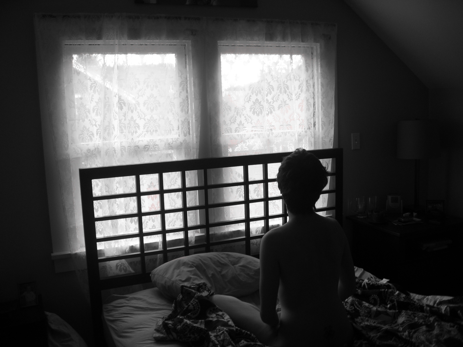 Silhouette of someone sitting on a bed by a window
