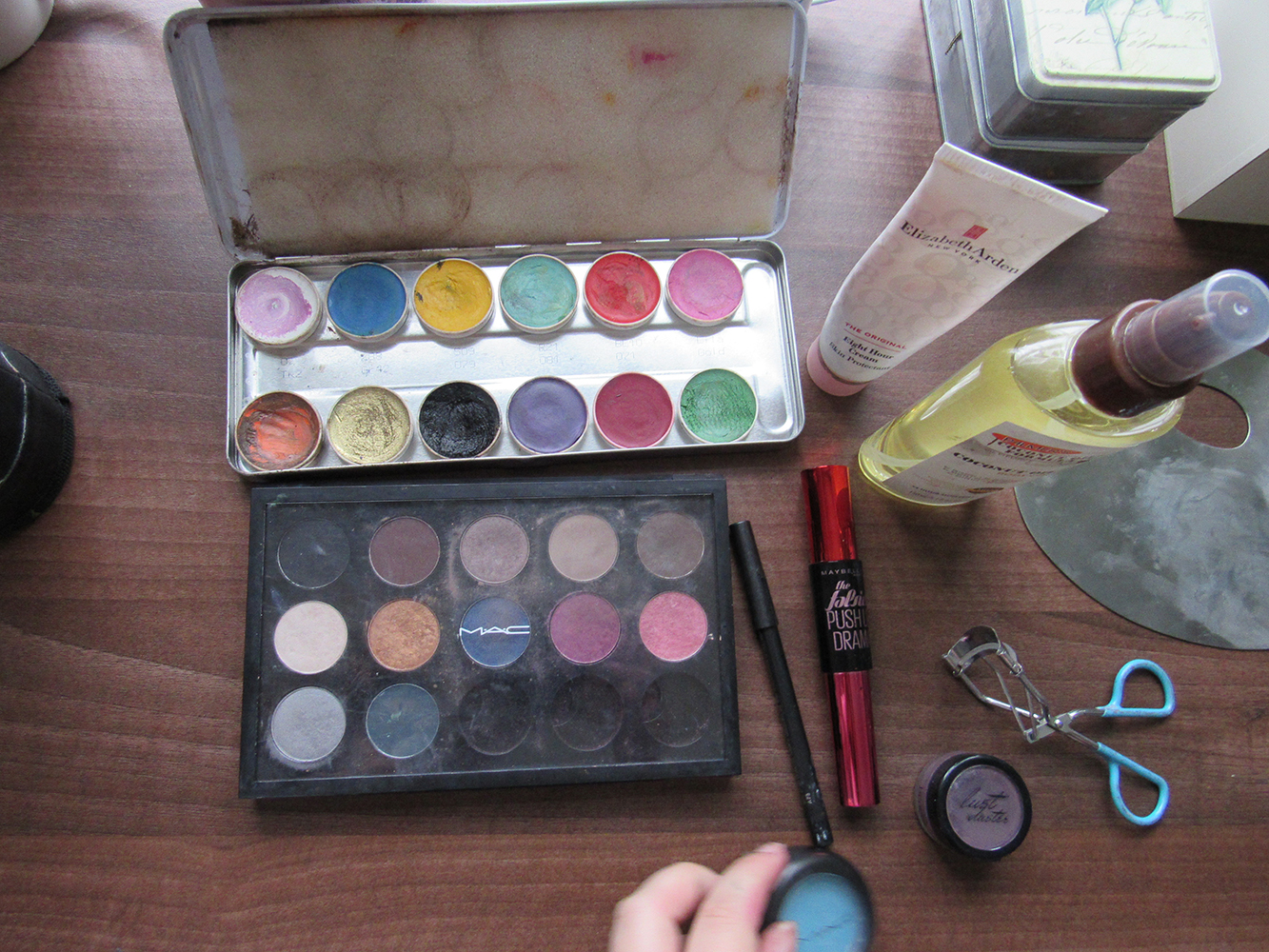 Makeup brushes, eyeshadows and other utensils on a table
