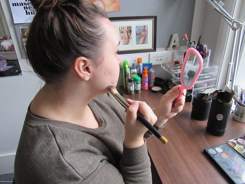 Girl is sitting in front of a desk holding a mirror and putting makeup on