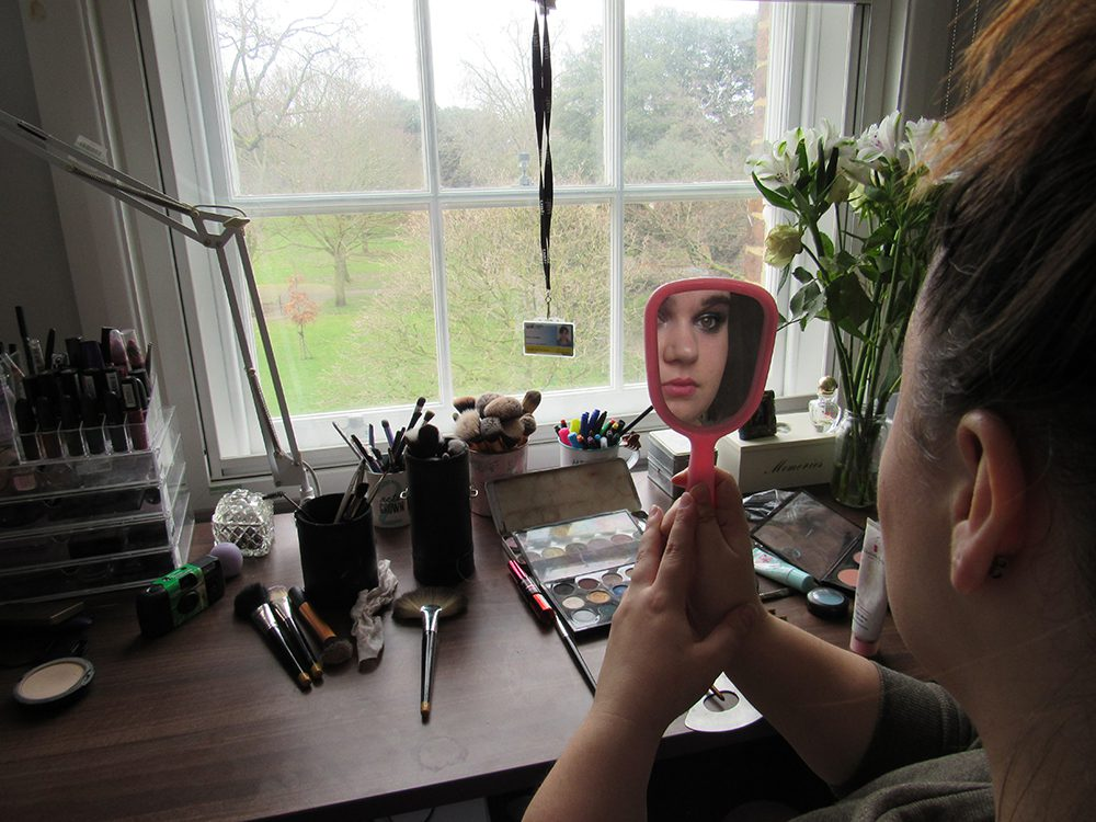 A girl looks into a mirror