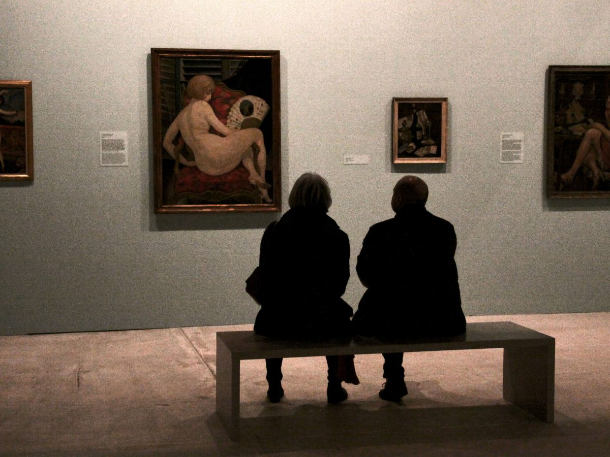 Two people sitting in an art gallery