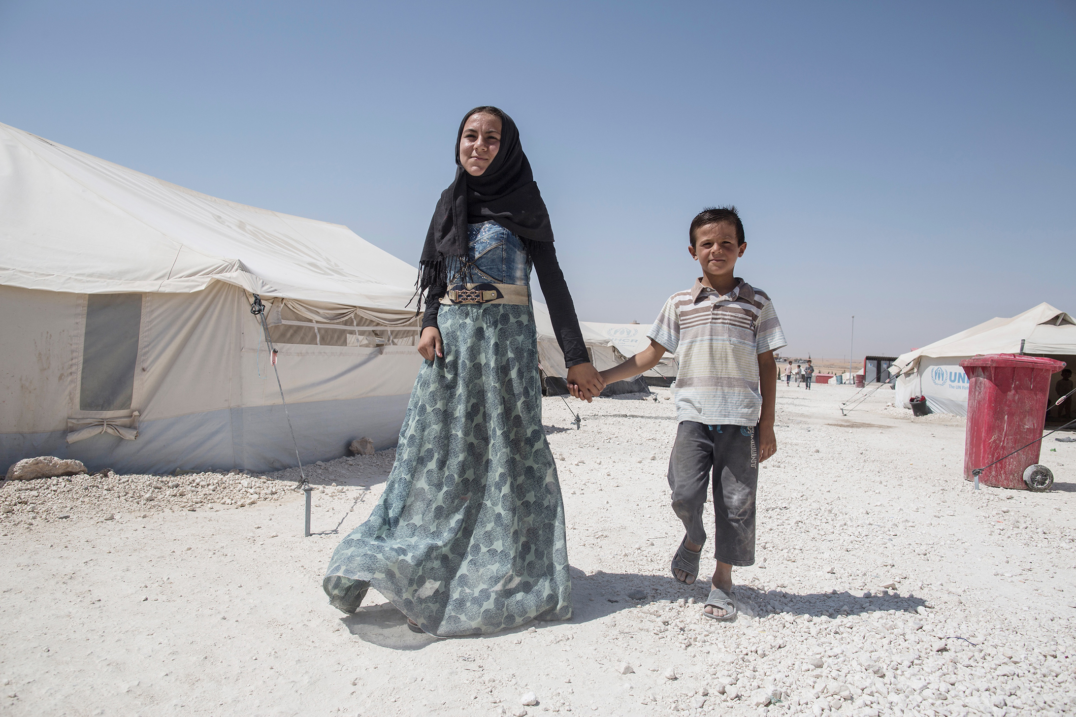 Raashida, 13, walking with her younger brother