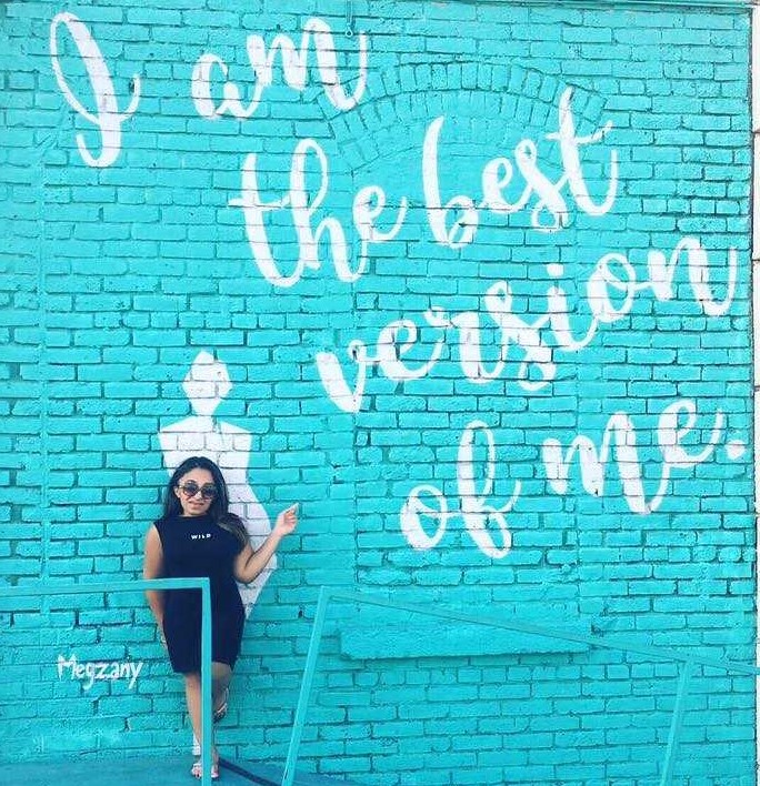 """Woman posing by graffiti which reads """"The best version of me."""""""
